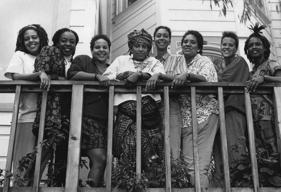 8 members of the ACHÉ publication standing against a railing smiling.