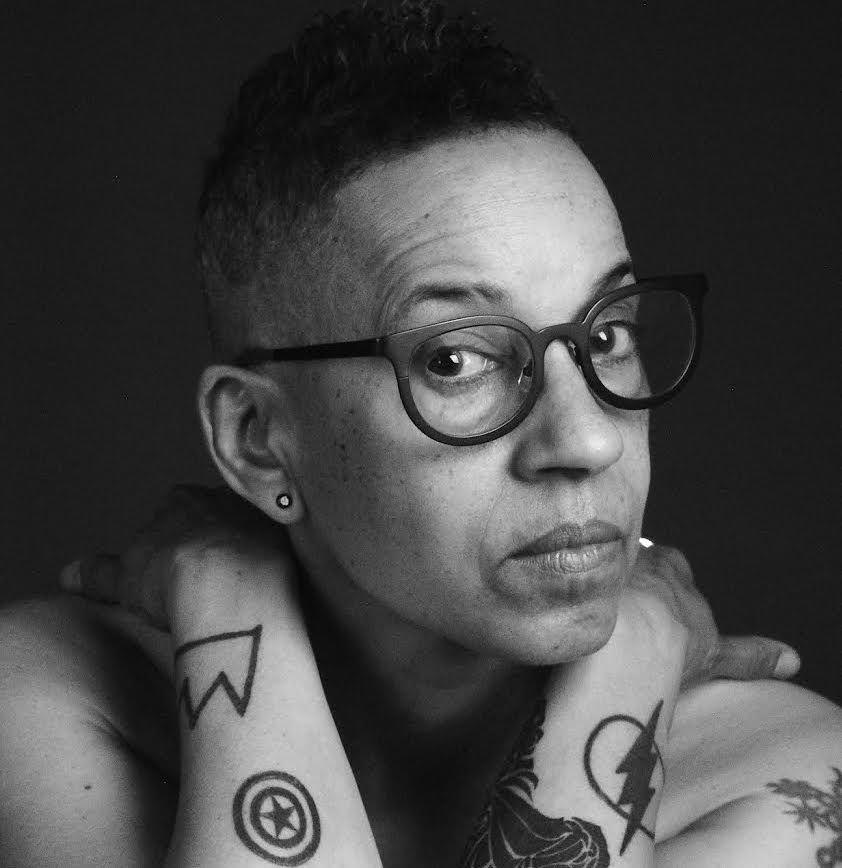 Black and white portrait of Lola Flash, wearing their hair short, dark rimmed glasses and holding their hands on their shoulders.