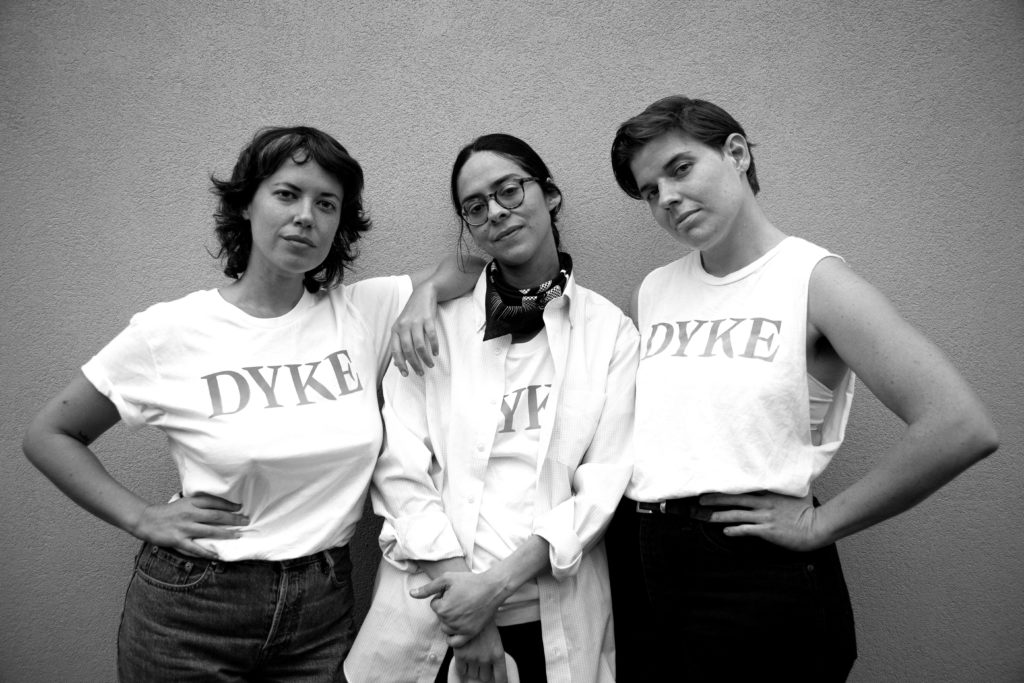 WMN founders Jeanette Spicer, Florencia Alvarado, and Sara Duell wearing white dyke t-shirts standing next to each other looking into the camera