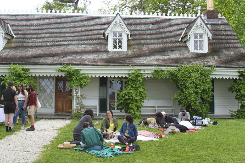 View of the Alice Austen House and people hanging out in a picnic.