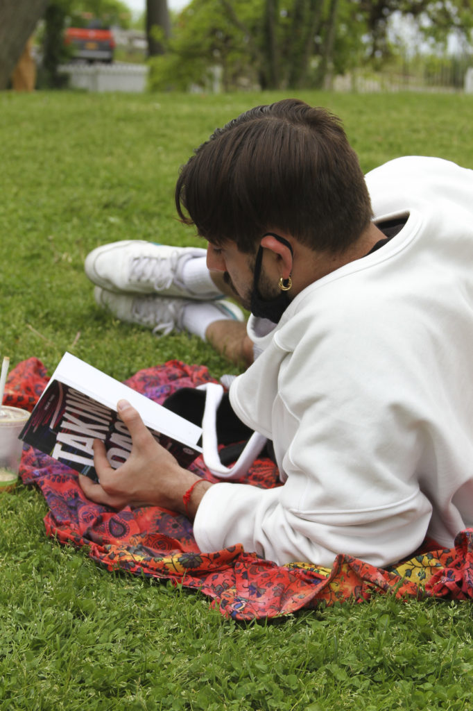 Man laying in the grounf reading our Third Isuue.