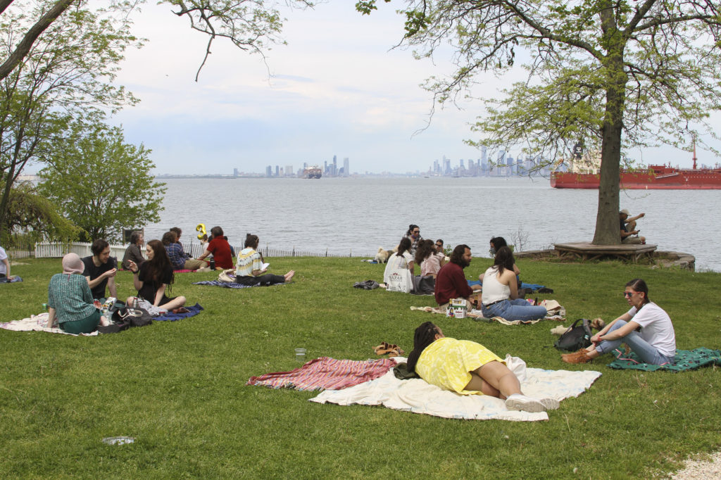 View of Manhattan and people hanging out in a picnic at the Alice Austen House Museum.